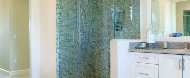 White bathroom with blue and green tiled shower