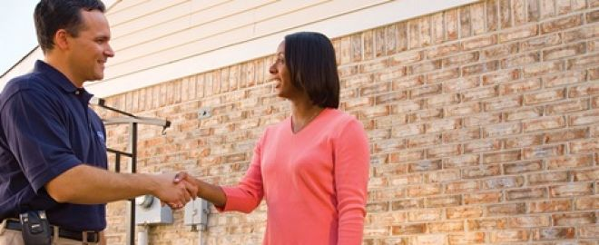 Sears HVAC expert shakes hands with woman in pink shirt in front of new AC units