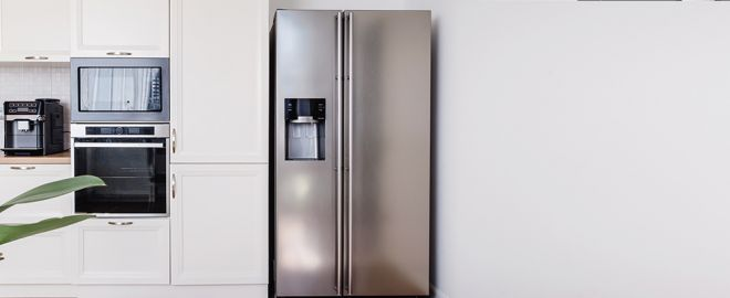 Stainless steel fridge in minimal, white kitchen