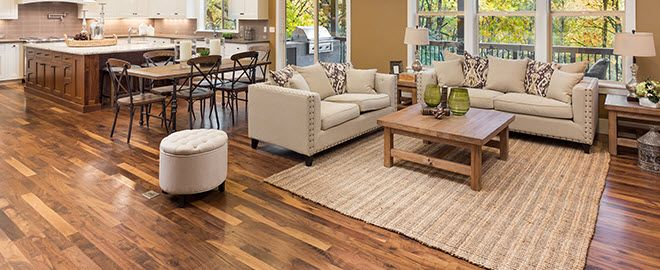 Spacious tan living room with brown faux-bois flooring