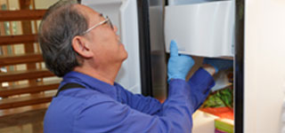 Sears Home Services refrigerator repairman fixes a problem with a customers refrigerator ice maker